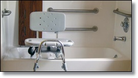 The bathtub has grab-bars, folding seat and flat back